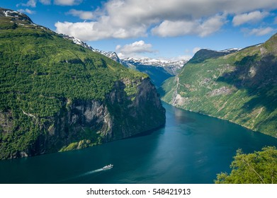Cruising ship is going to North Sea by narrow fjord water channel, surrounded by steep mountains. Aerial photo of Geiranger fjord, Norway.