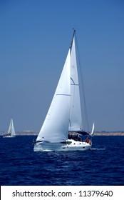 Cruising yachts in mediterranean sea on blue sky background