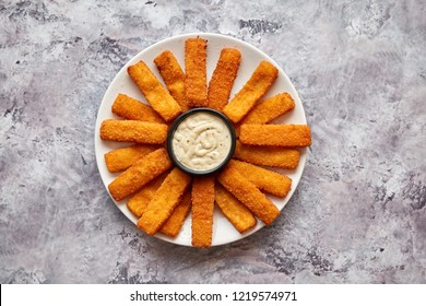 Crumbed fish sticks served with garlic dip sauce on a white plate on a stone table. Top view with copy space.