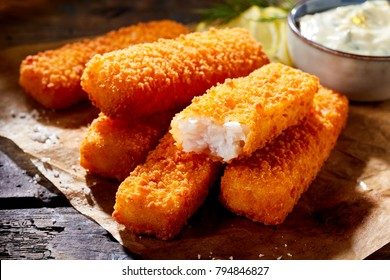 Crumbed golden fried fish fingers in sticks served on brown paper on a rustic wood counter with tartare sauce in a close up view with one broken open