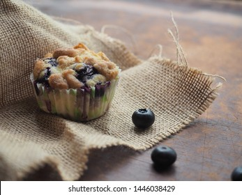 Crumble blueberry muffin on sackcloth on wooden table.