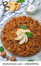 Crumble with pear, cinnamon, walnuts and Greek yogurt in a glass baking dish on a white wooden table. Top view.