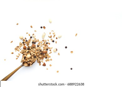 Crumbled granola with a wooden spoon on a white background. Top view, isolated in white.