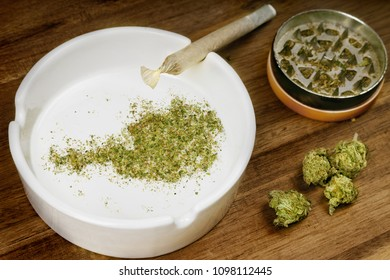 Crumbled weed in the shape of Austria and a joint. (series)