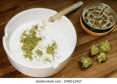 Crumbled weed in the shape of Denmark and a joint. (series)