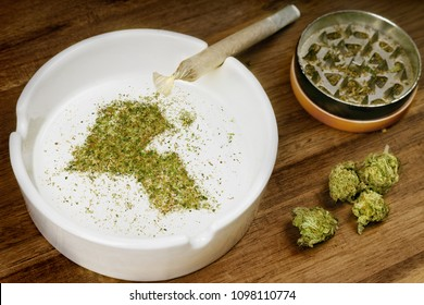 Crumbled weed in the shape of Kuwait and a joint. (series)