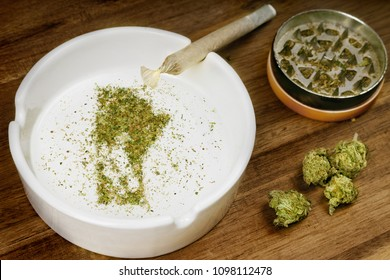 Crumbled weed in the shape of Manitoba and a joint. (series)