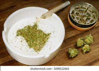Crumbled weed in the shape of New Brunswick and a joint. (series)