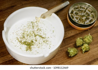 Crumbled weed in the shape of Nunavut and a joint. (series)