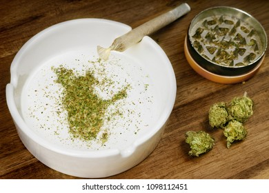Crumbled weed in the shape of Quebec and a joint. (series)