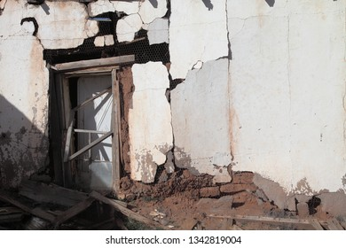 Crumbling adobe walls and doorway of a very old house on the high plains of New Mexico.