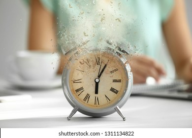 Crumbling alarm clock on white table in office
