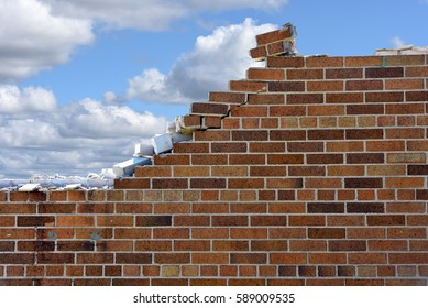 crumbling brick wall with fluffy clouds and blue sky background