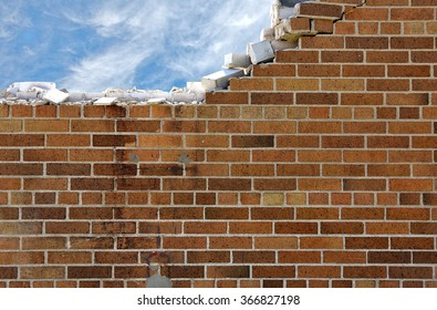 crumbling brick wall with white wispy clouds in blue sky