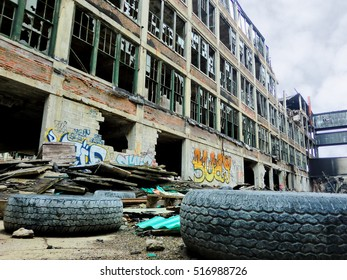Crumbling industrial factory exterior in Detroit, Michigan with tires