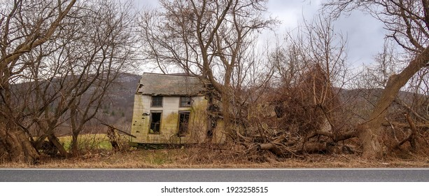 Crumbling old house on the side of the road. Winter season.