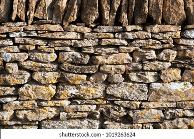 Crumbling old lichen covered Cotswold drystone wall texture