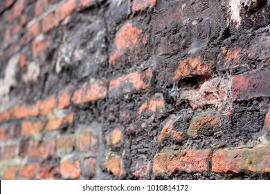 a crumbling old red brick wall background texture in shallow depth of field. stone wall selective focus