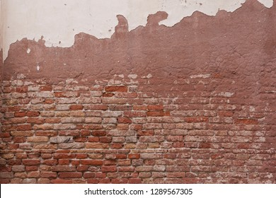 A crumbling old wall in Venice. Showing exposed bricks and neglected plaster work. Most of the brickwork is orange in colour.
