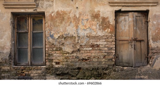 A crumbling wall with two old windows.