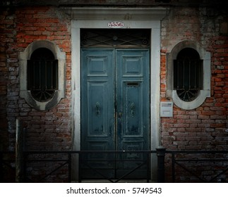 Crumbling weathered entrance to a building in Venice, Italy, with red brick wall, ornate barred windows and blue wooden door.
