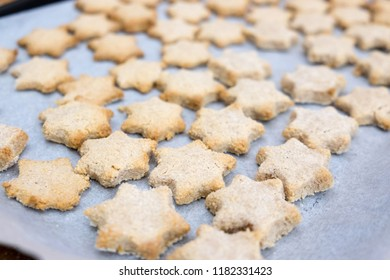 Crumbly messy star shaped cinnamon Christmas cookies lightly baked till golden brown on baking paper with shallow depth of field