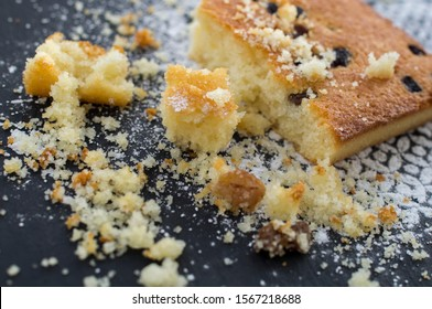 crumbly piece of cake from semolina on the background of a large piece with raisins on a black background