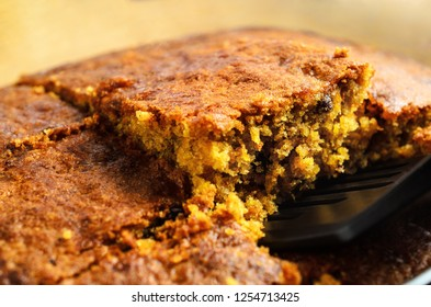 A crumbly square slice of freshly baked carrot cake being lifted from baking dish for serving. Close up just above eye level.