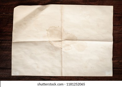 Crumpled aged folded letter with spot and stain on Dark wooden table