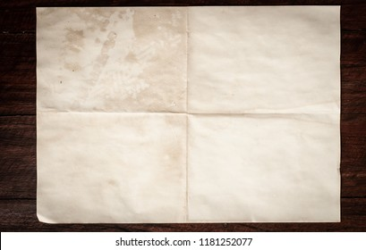 Crumpled aged letter sheet with spot and stain on Dark wooden table