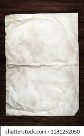 Crumpled aged paper with spot and stain on Dark wooden table