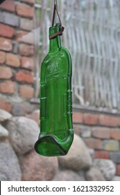 crumpled bottle of beer hanging on the background of stones