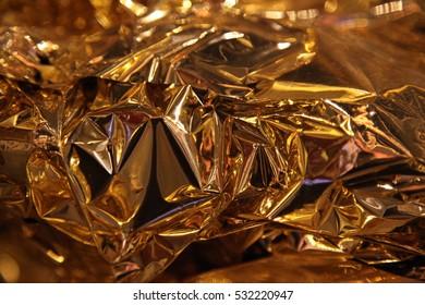 Crumpled bronze foil texture background. Shiny leaf bronze foil