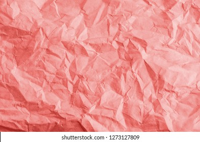 Crumpled, creased and unfolded paper background texture in a coral hue.