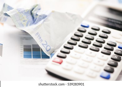 Crumpled Euro banknotes with calculator and charts