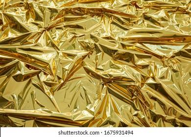 Crumpled, golden metallic foil texture background