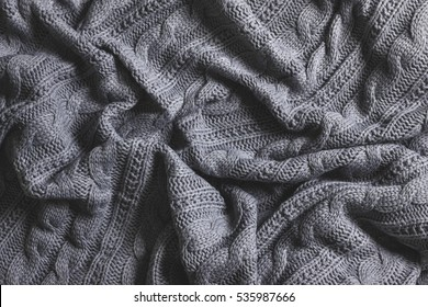 Crumpled gray knitted blanket. Soft and warm fabric crumpled in folds. Texture for background or illustrations