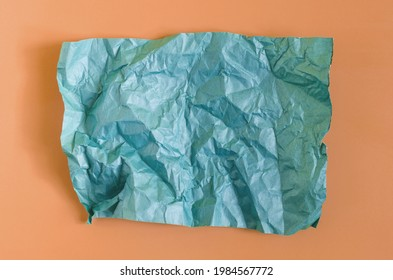 Crumpled green paper on an orange background. The texture of the crumpled paper for the background.