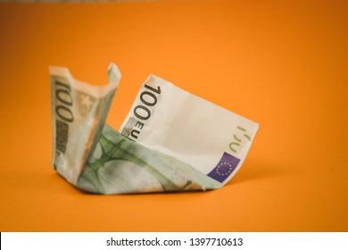 crumpled hundred euro lying on orange background