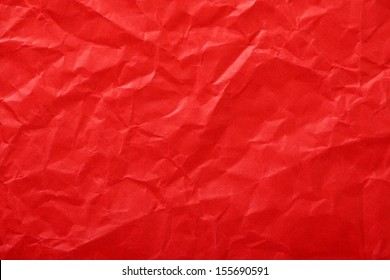 Crumpled paper background made from a blood red sheet of wrapping paper.
