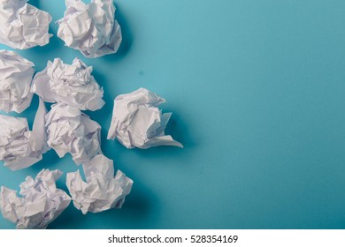 crumpled paper ball isolated on a blue background