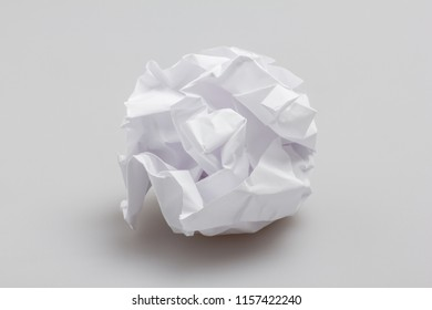 Crumpled paper ball lying on gray background. Recycling or creativity concept.