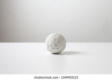 Crumpled paper ball on white. Papier mache. Craftwork on white background.