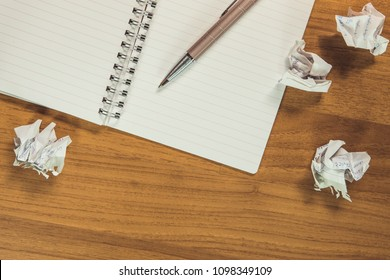 crumpled paper and notebook and pen on the wooden