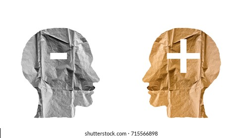 Crumpled paper shaped as a human heads and plus and minus signs. Positive and negative concept.