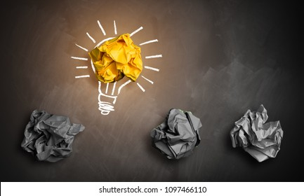 crumpled paper symbolizing different solutions with one highlighted as a light bulb as the right one
