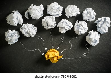 crumpled paper symbolizing different solutions with one standing out with a different color as a combination of the best ideas