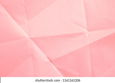 Crumpled paper texture in soft pink composed as a background.