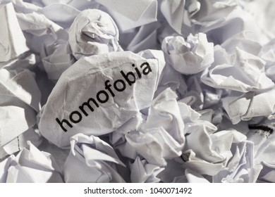 Crumpled paper written homofobia, portuguese and spanish word for homophobia. Illustrative concept of ideology thrown into the trash. Old and abandoned idea or practice. Close up, macro photography.