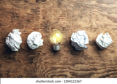 Crumpled papers with light bulb on wooden background. Idea
